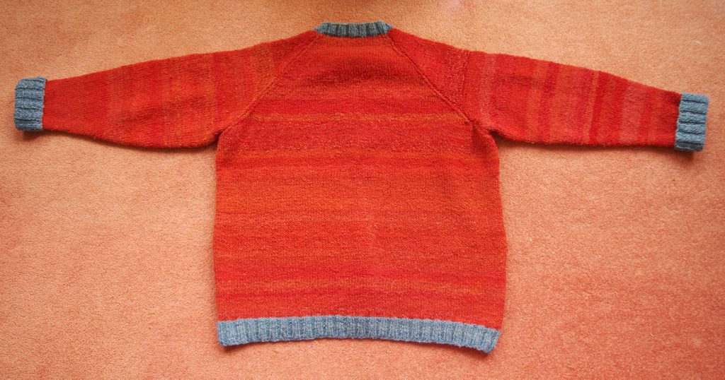 shows rear of red madder dyed jumper with red stripes - the result of uneven dyeing